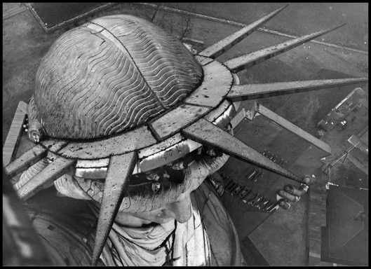 Visitors peek out from under the crown of the Statue of Liberty